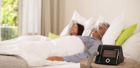 СИПАП-терапия: пацент в маске спит с подключенным сипап-аппаратом дома.