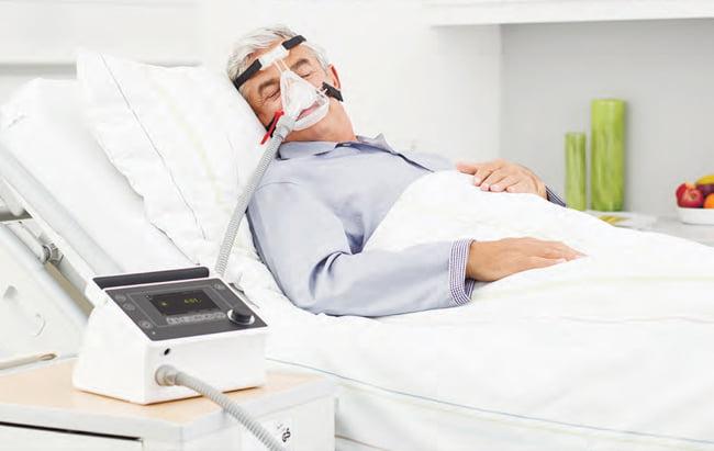 Неинвазивная вентиляция легких: пациент в маске, аппарат ИВЛ Prisma VENT