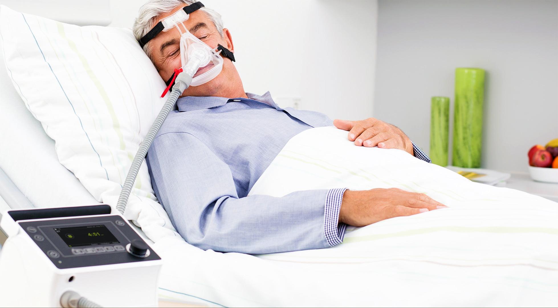 Аппарат неинвазивной вентиляции легких ИВЛ и НИВЛ Prisma VENT 30 / 30-C пациент спит в кровати мужчина в маске