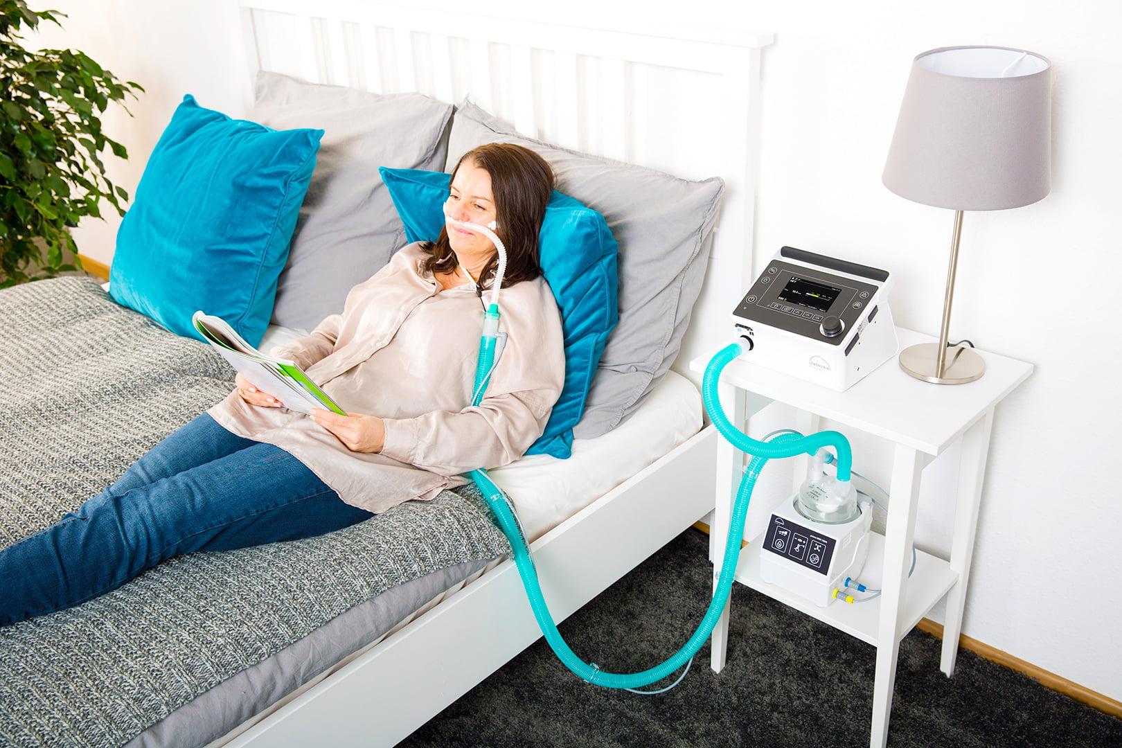 Женщина лежит в кровати Аппарат ИВЛ и НИВЛ неинвазивной и инвазивной вентиляции легких Prisma VENT40, Prisma AQUA