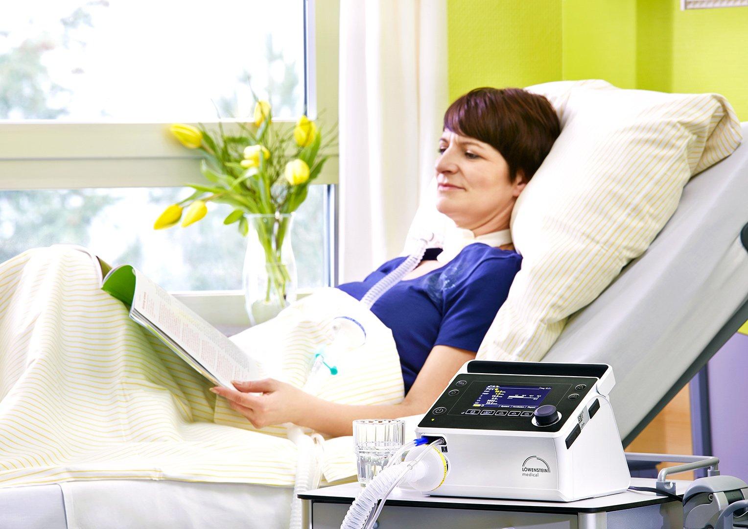 Аппарат ИВЛ Prisma VENT50 женщина лежит в кровати контур пациента вентиляция легких