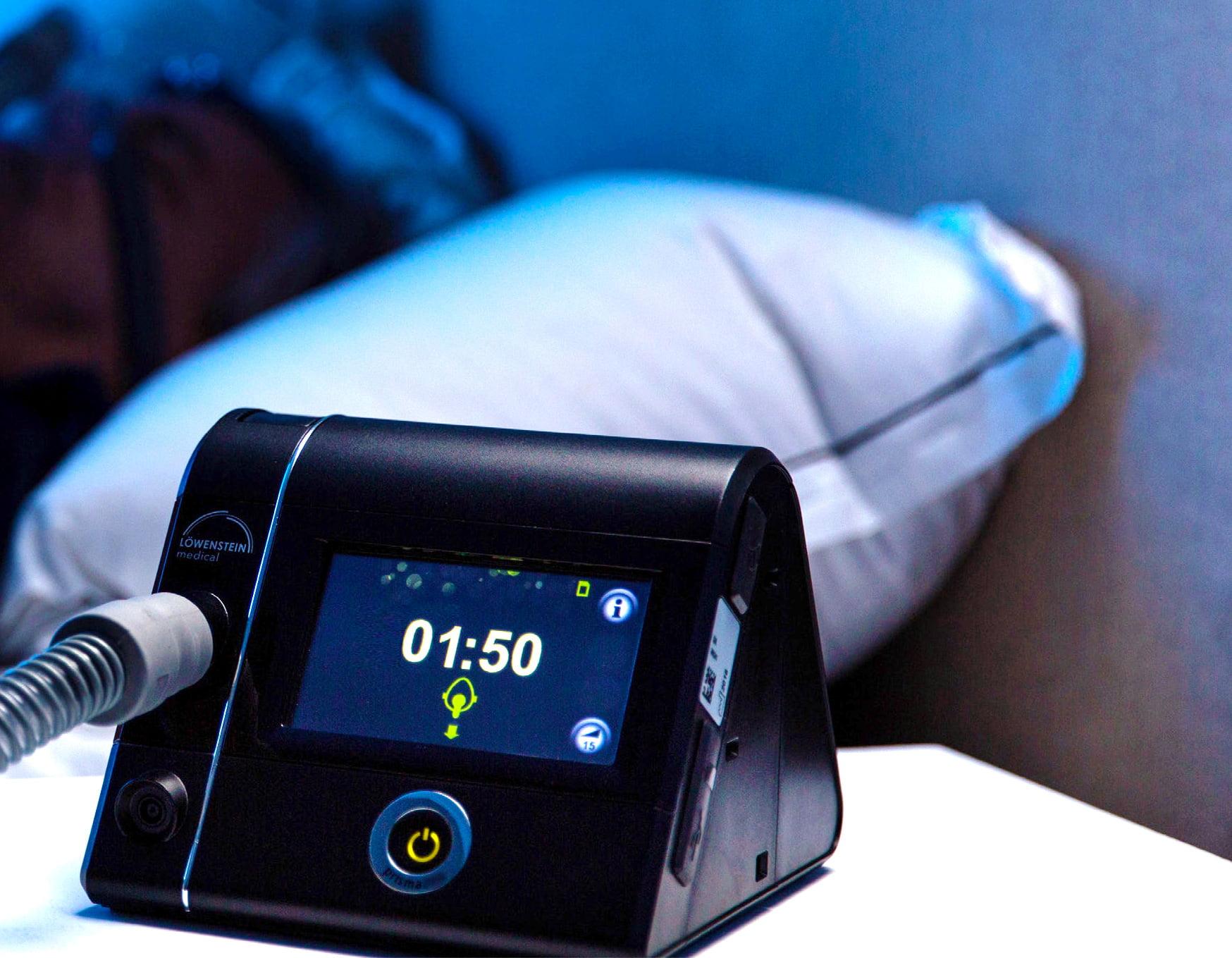 Аппарат для титрации Prisma LAB - в спальне, пациент спит в маске на кровати