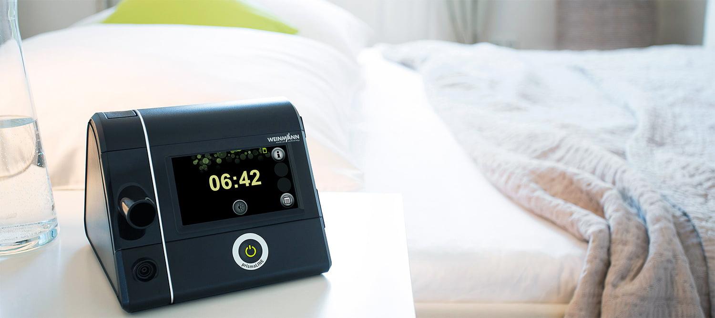 Сипап-аппарат Prisma 20A стоит на тумбочке возле кровати в спальне.