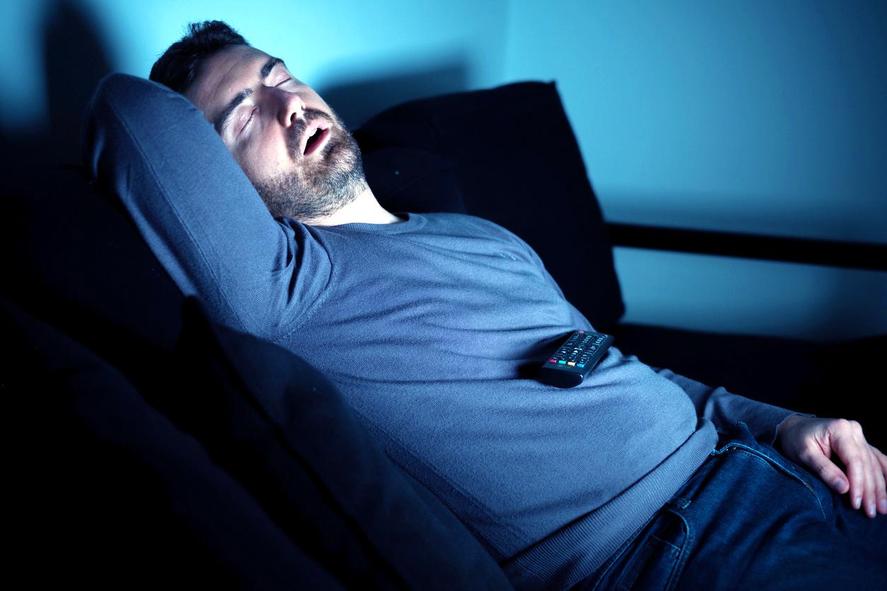 Мужчина храпит перед телевизором. Просмотр телевизора увеличивает риск апноэ во сне.