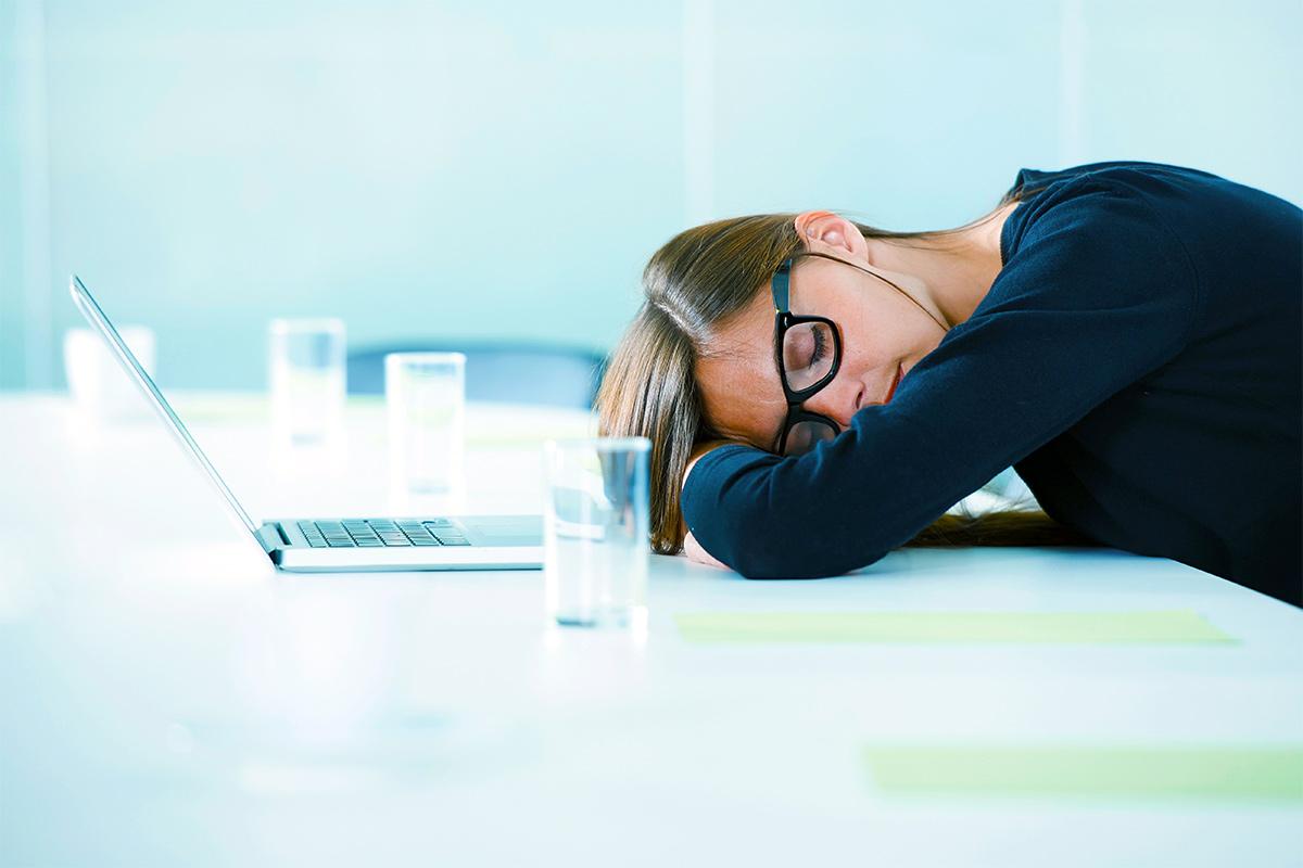Гиперсомния (сонливость): причины, как лечить, кто лечит. Девушка спит перед ноутбуком, на работе, на рабочем месте.