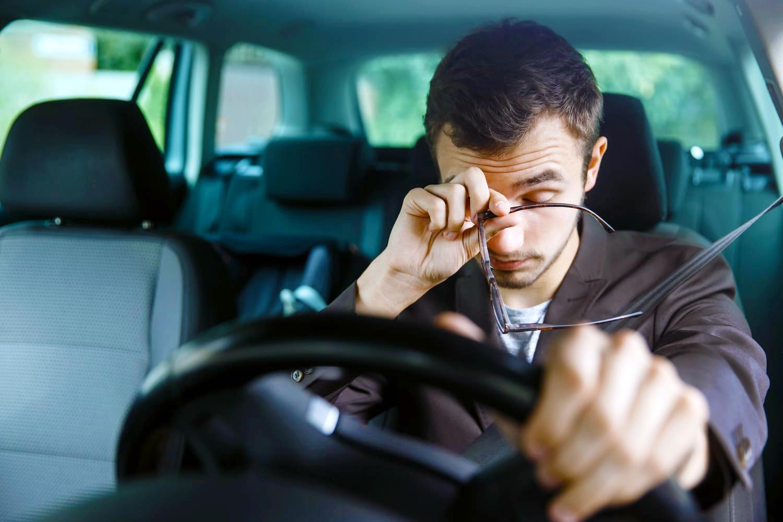 Нарколепсия и вождение. Мужчина спит за рулем, в автомобиле.