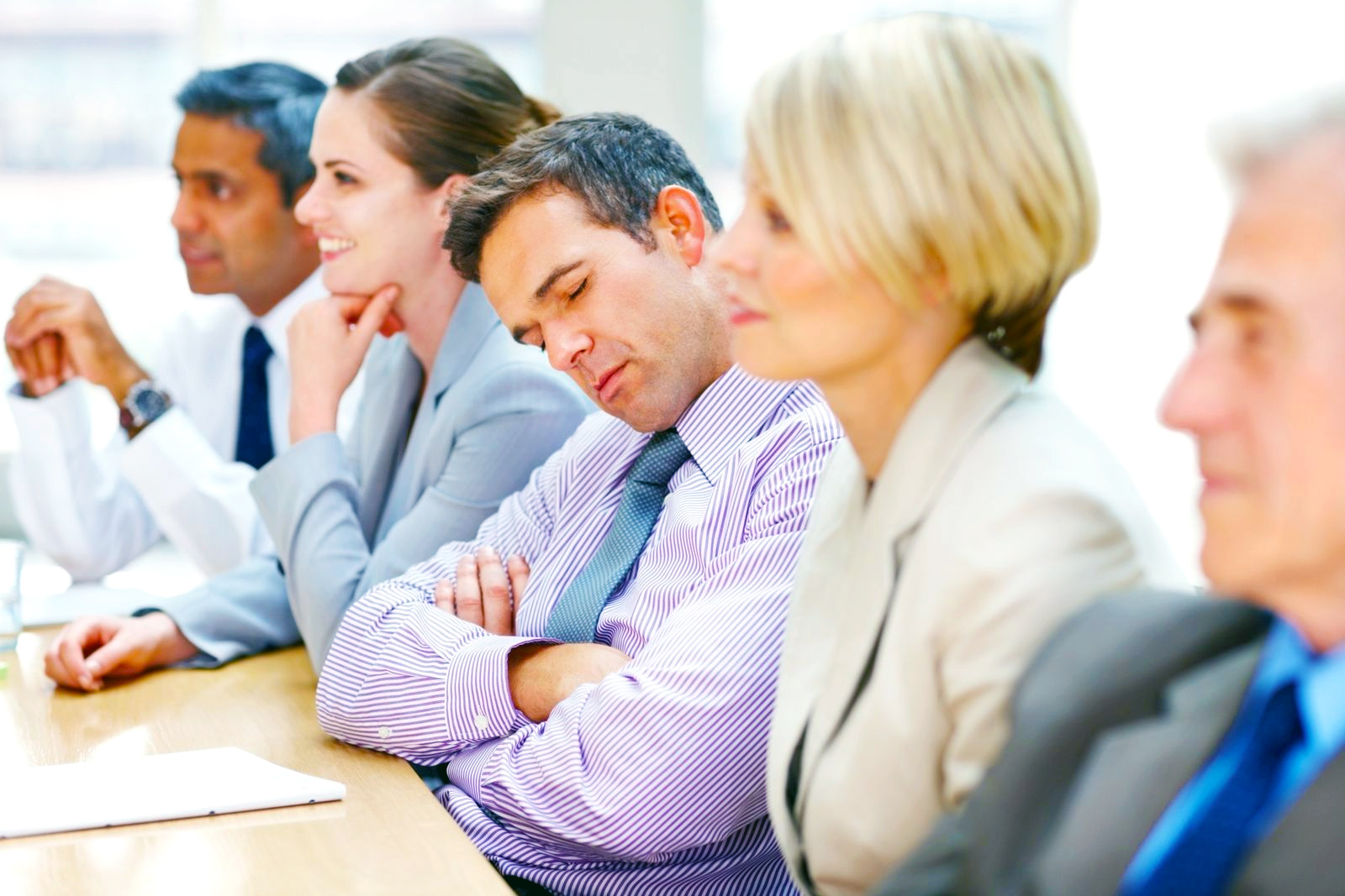 Симптомы нарколепсии: мужчина спит на совещании компании в офисе.