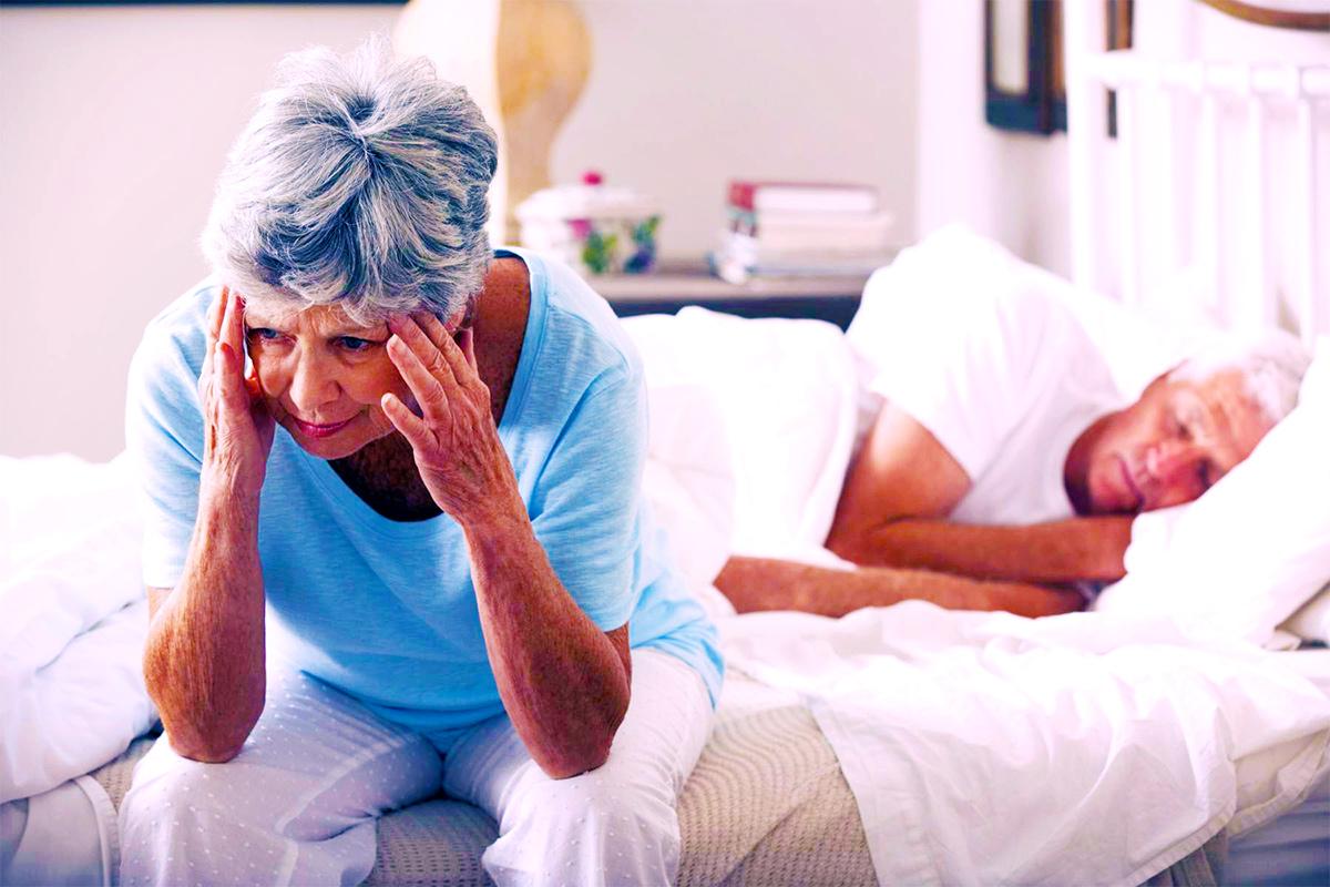 Нарушение сна, женщина не может уснуть сидит на кровати, муж спит. Бессонница, апноэ во сне, нарушения циркадного ритма, синдром беспокойных ног,гиперсомния, парасомния